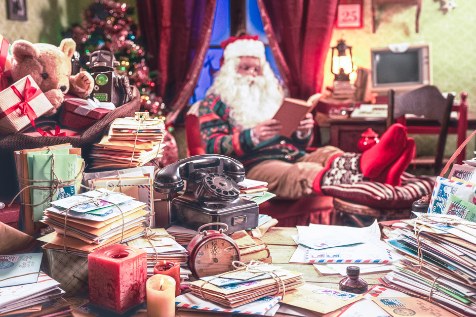 The messy desk of Santa Claus, he reading a book